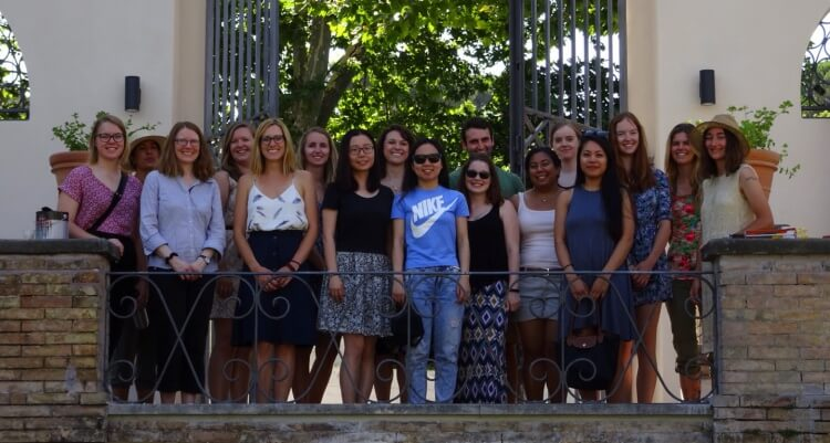 Diverse group of 16 students and two professors in front of large iron gates with greenery in background