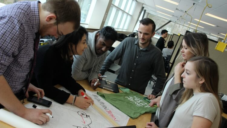 Diverse group of 6 planning students surround a drafting table