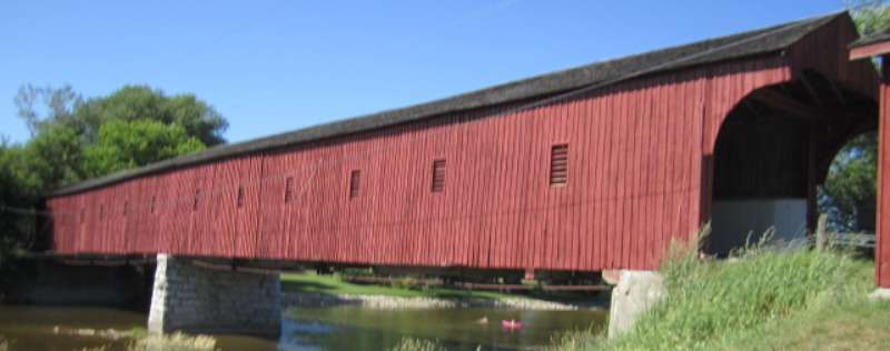 Red covered bridge stretching over a river