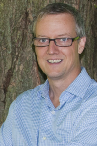 Man with grey hair and glasses, leaning against a tree