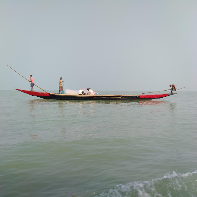 fishermen standing on long boat