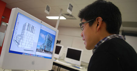 A student works on a 3D model of a building.