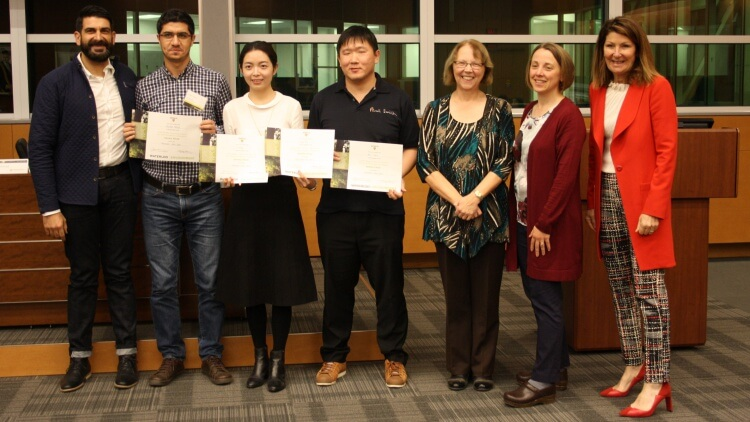 Four judges standing with three students holding certificates and smiling
