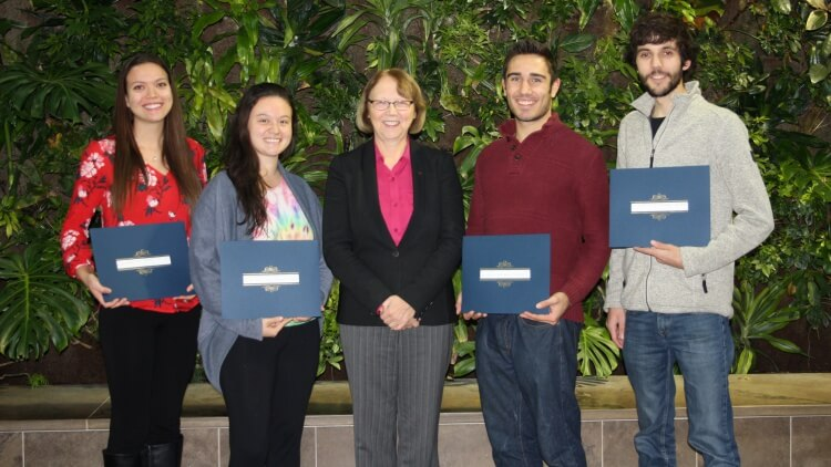 2 female and 2 male students, all smiling and holding awards, posing with professionally dressed female