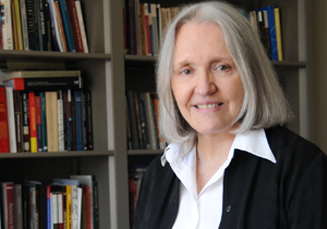 Saskia Sassen standing in front of a bookshelf