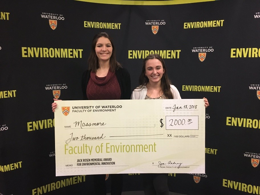 Two winning students holding a giant novelty cheque