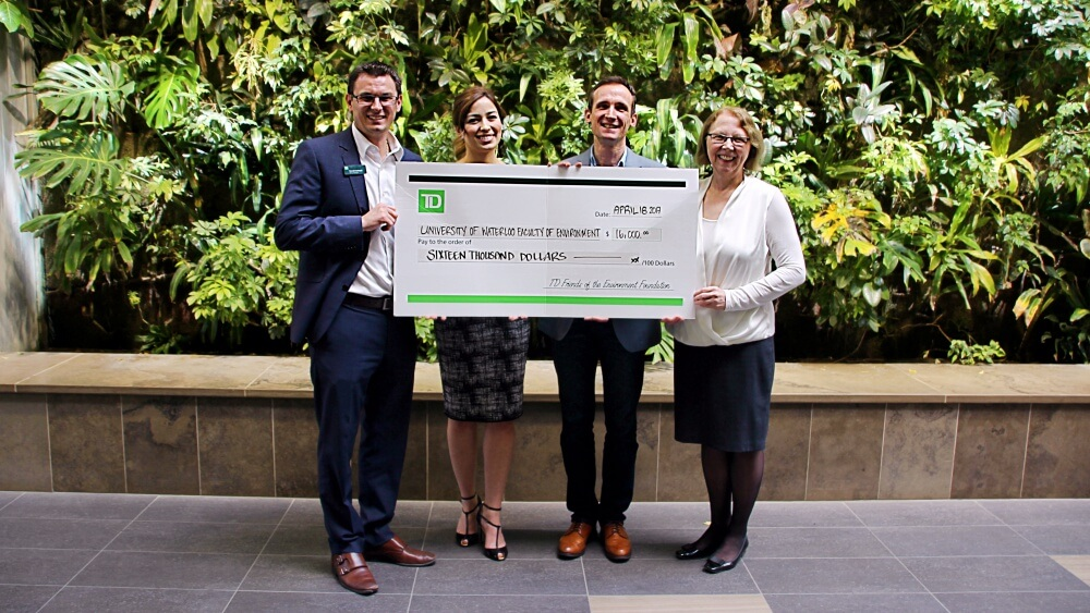 Four professionals, 2 male and 2 female, holding a large presentation cheque in front of a green living wall