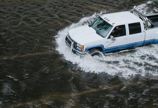 A truck driving through a flooded road
