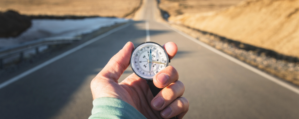 A person's arm, with a compass in their hand. A road stretches out in front of them.
