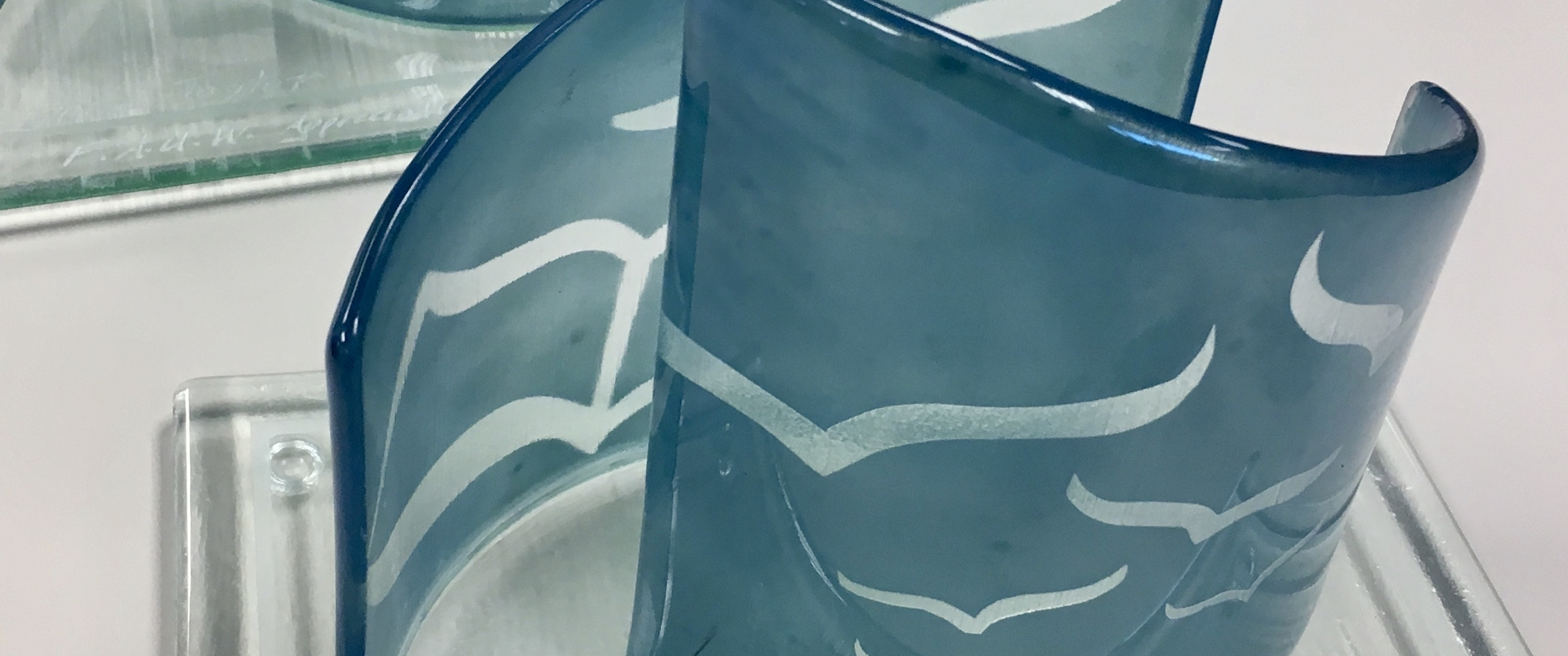 the award is made of two curved pieces of blue glass etched with the book and flying pages/birds from the FAUW logo.