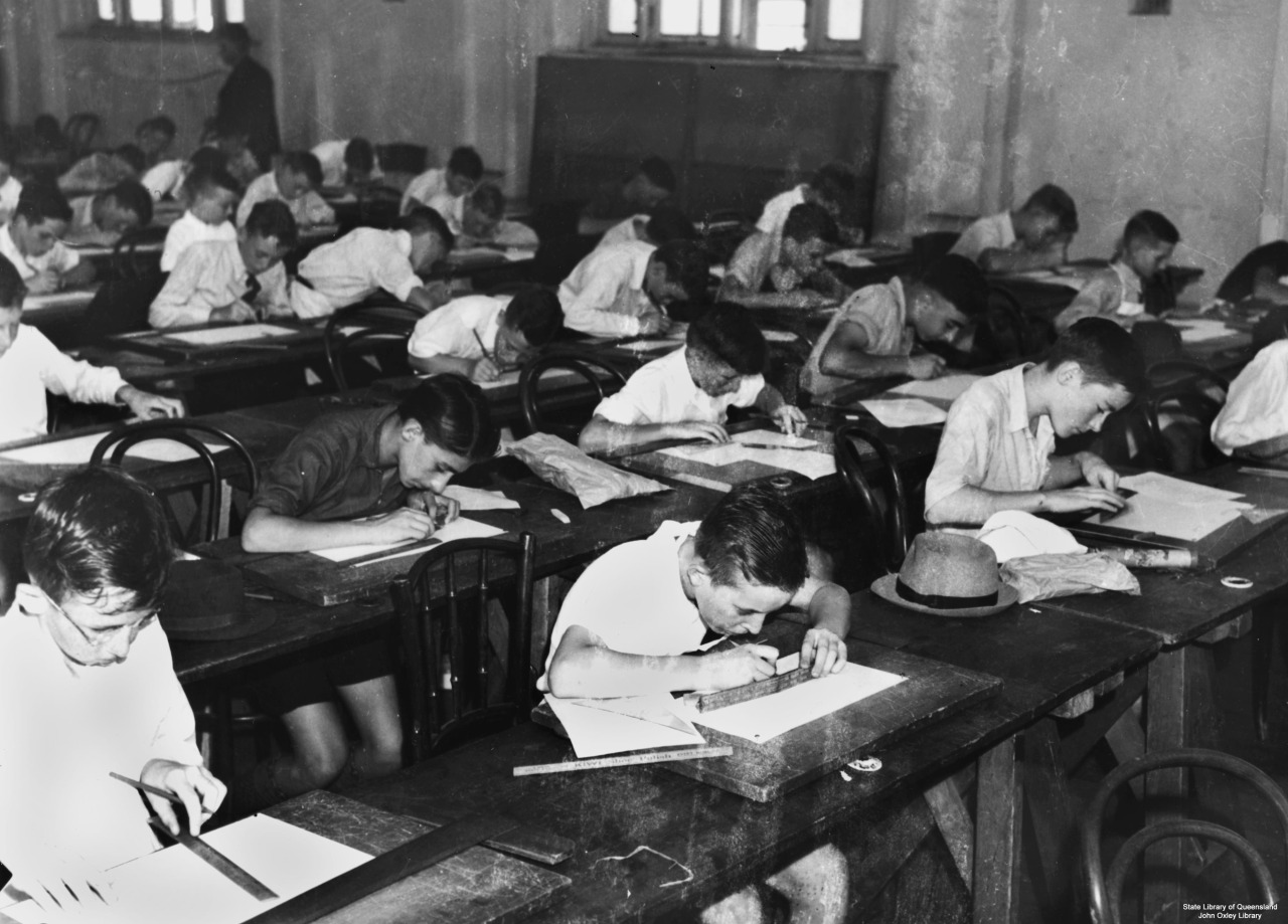 An old black and white photo of students writing at their desks.