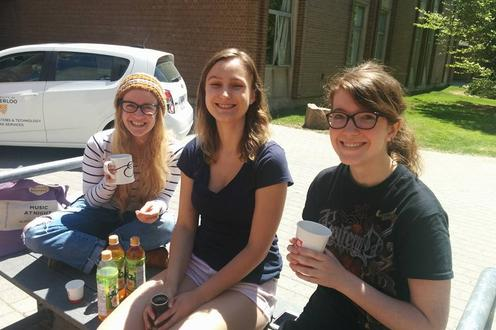 Three woman sit on a bench outside hold various mugs and cups. On the bench there are also three bottles of iced tea.