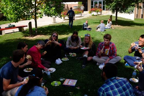 A group of young adults sit on the grass. In front of them is an assortment of food on foam plates.