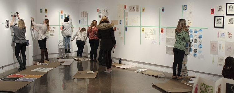 Students installing a print show in the artery gallery