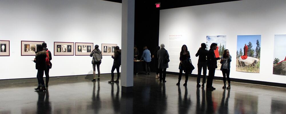 Visitors in the UWAG art gallery viewing photographs