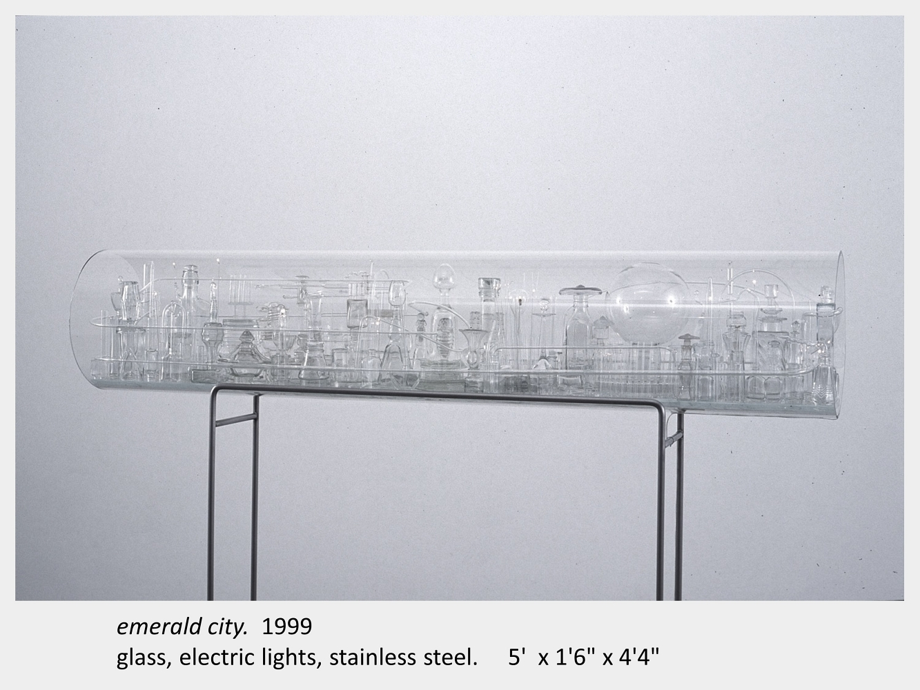 "Artwork by Lois Andison. Emerald city. 1999. glass, electric lights, stainless steel. 5'x 1'6"" x 4'4"""