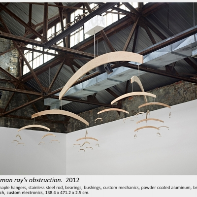 Artwork by Lois Andison.  solving man ray's obstruction.  2012, Routered maple hangers, stainless steel rod, bearings, bushings