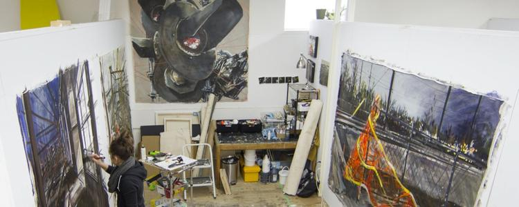 Aerial view of a graduate student working on a painting in her studio