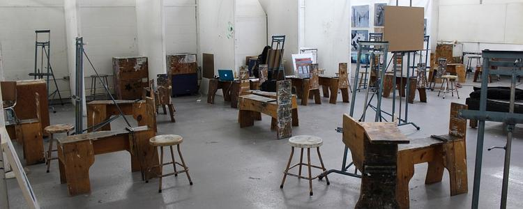"""View of the painting studio in East Campus Hall with easles and drawing """"donkeys"""" spread around the room."""