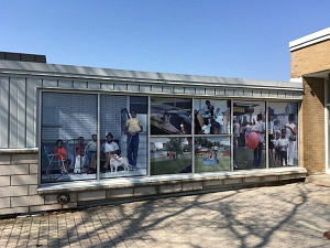 Large scale photographic installation of family photos from the 1960s on building windows.