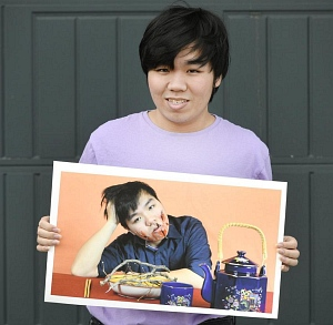 David Nguyen holding a digitally altered photographic self portrait