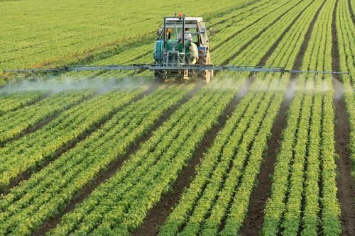 truck spraying field with pesticide