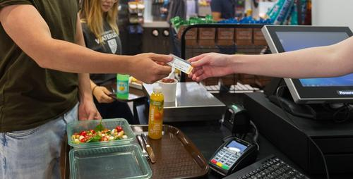 Man giving watcard to cashier in servery