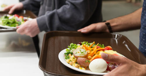 Student holding a plate of food with eggs, vegetables, fruit