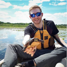 Applied Health Sciences student in a boat on a lake holding a turtle while smiling at the camera