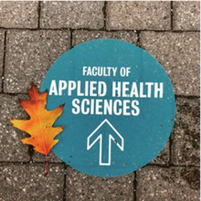 Applied Health Sciences decal on the ground outside with an orange leaf beside it