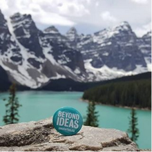 Teal Applied Health Sciences pin in foreground with mountains and a lake in background