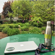 laptop and waterbottle with Faculty of Environment decorations sit on a table with many trees and bushes around