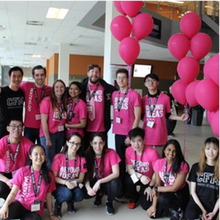 group of students wearing pink Faculty of Math shirts with balloons in the background