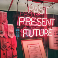 "showcase with pink ties and ""past present future"" in neon pink letters on the outside"