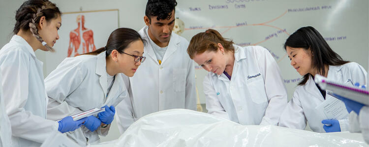 Professor and students looking at cadaver on table