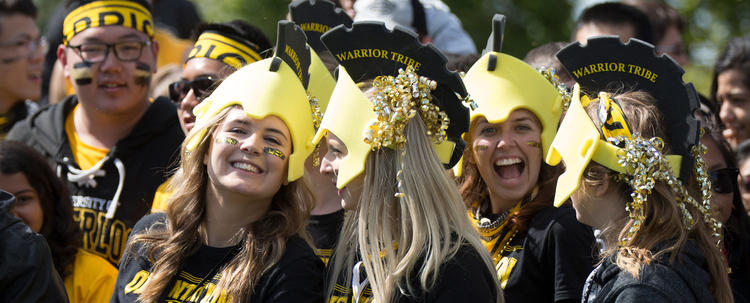 Students wearing black and gold at University of Waterloo football game