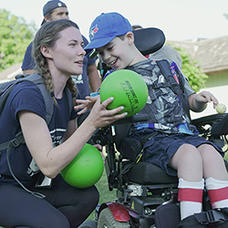 Co-op student giving ball to child in wheel chair
