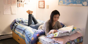 Female student reading book on her residence bed