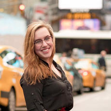 Hannah in New York City with taxis in background