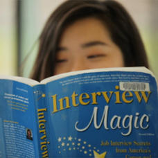 Student peeking over top of interview book