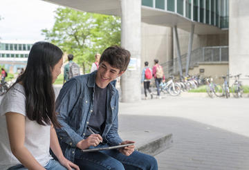 Students sitting on a bench at the University of Waterloo