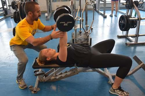 Sports Management student helping another student with lifting weights.