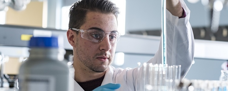 A student in one of Waterloo's Physical Sciences programs works with a pipette in a lab