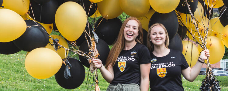 Two Waterloo student ambassadors laughing and holding lots of balloons