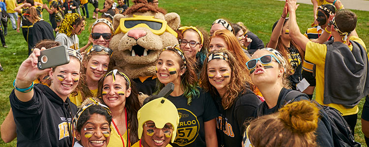 Group of students in black and gold taking selfie during fall orientation