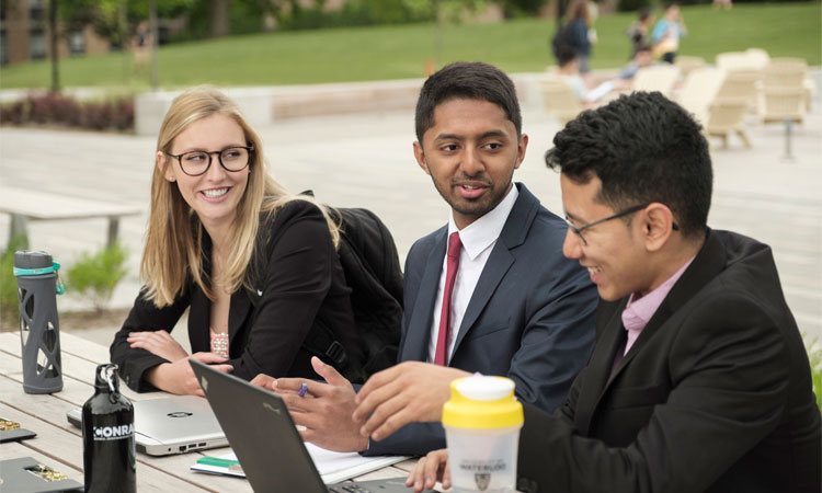 University business degree students with laptops sit outside at the University of Waterloo