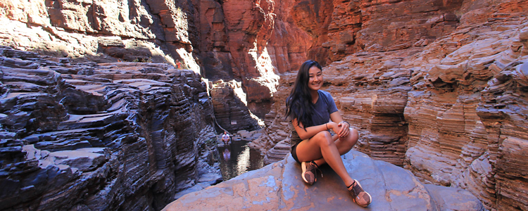 Study abroad student sitting on rock in canyon
