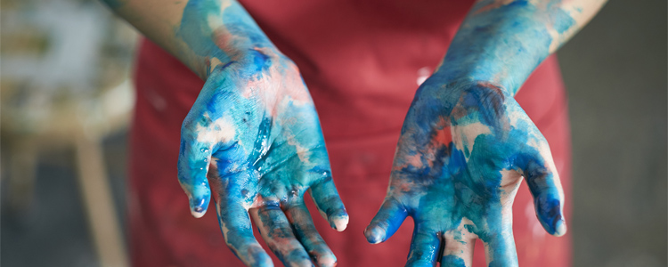 Hands of a student in the Fine Arts degree program at the University of Waterloo are covered in paint