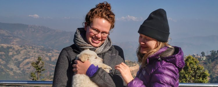 Carlee, a student in the international development degree program, holds a dog with a friend in Nepal.