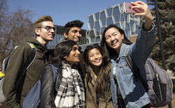 group of five students taking a selfie together